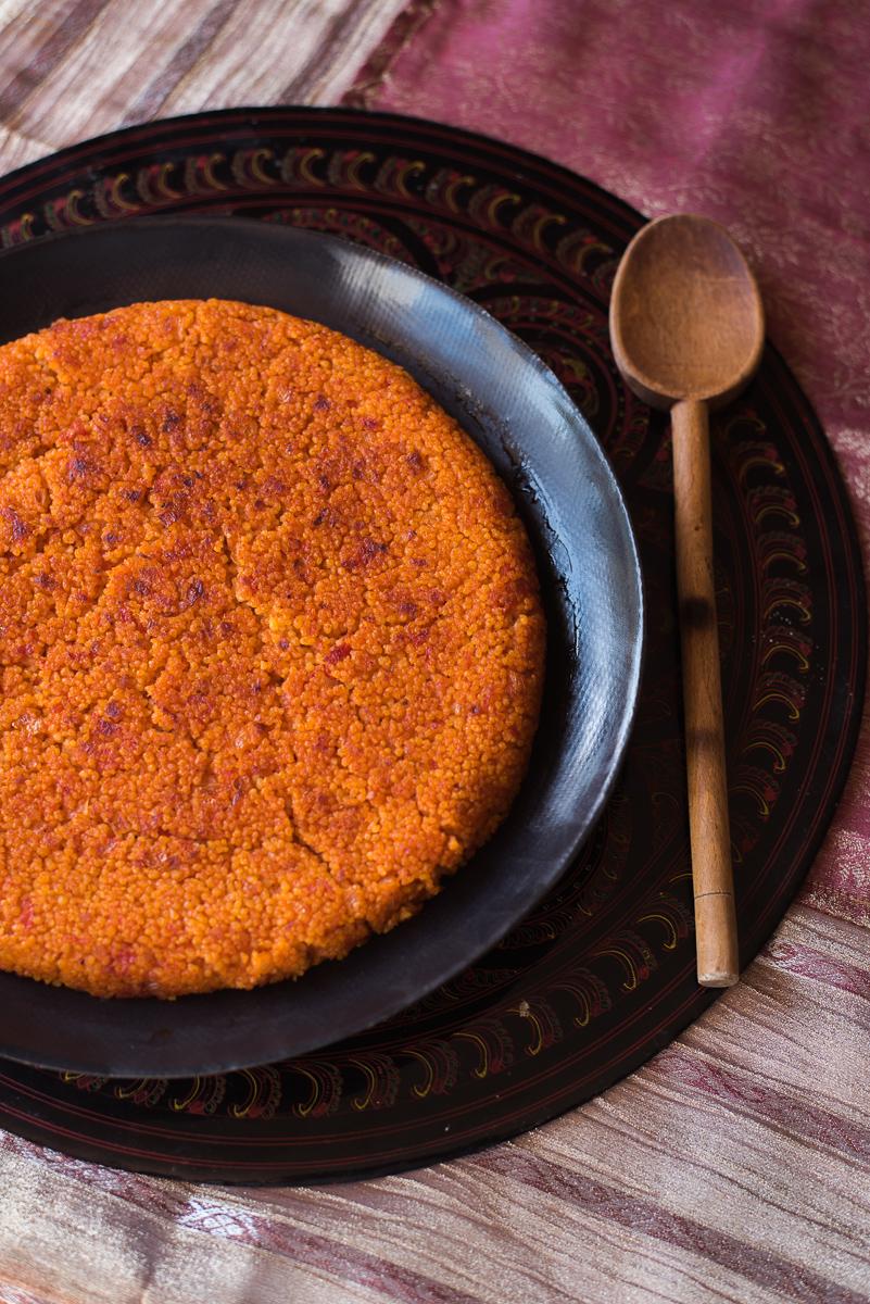 Couscous rosso con pomodori e cipolla di Ottolenghi su piatto e sottopiatto vista aerea
