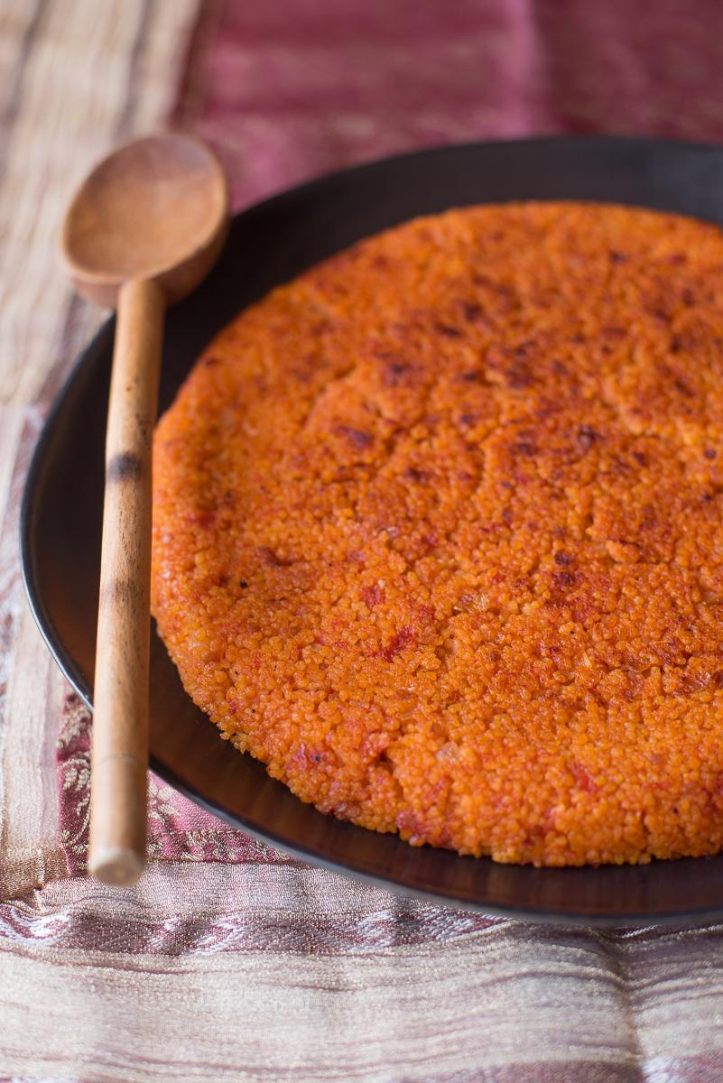 Couscous rosso con pomodori e cipolla di Ottolenghi su piatto con mestolo